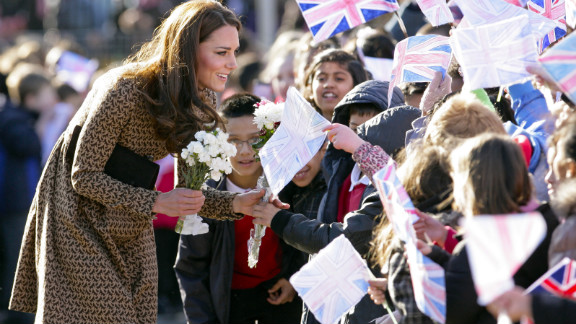 Catherine talks with flag-waving schoolchildren as she arrives for a visit to The Art Room