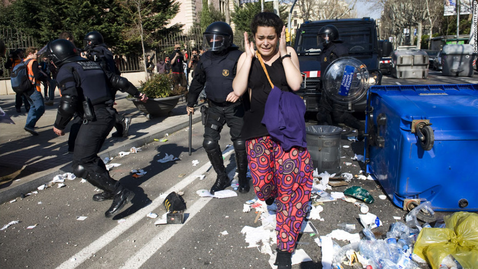 <strong>February 29: </strong>A protester runs for cover as riot police clash with students during a demonstration in Barcelona, Spain. Tens of thousands of students protested education cuts announced by the Catalan government.