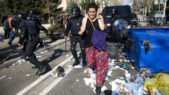 February 29: A protester runs for cover as riot police clash with students during a demonstration in Barcelona, Spain. Tens of thousands of students protested education cuts announced by the Catalan government.