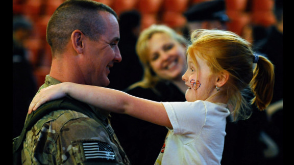 March 28: Sgt. 1st Class Paul Brady of the 182nd Infantry Massachusetts National Guard embraces his 6-year-old daughter, Regan, during a welcome home ceremony in Melrose, Massachusetts. The 182nd Infantry Regiment, one of the original units in the United States military, returned from a yearlong deployment in Afganistan.