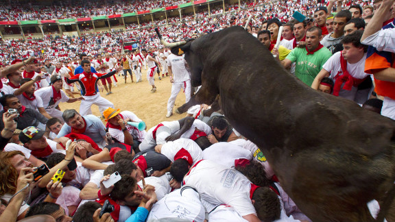 July 8: A wild bull hurdles over people blocking the animal