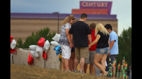 "July 28: Visitors gather and pray around a cross erected at a memorial set up across the street from the Century 16 movie theater in Aurora, Colorado. James Holmes is suspected of killing 12 people and injuring 58 others during a shooting rampage on July 20 at a screening of ""The Dark Knight Rises."""