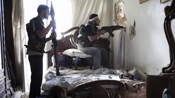 October 19: Free Syrian Army fighters watch a regime army position through a hole in a wall in Aleppo, Syria