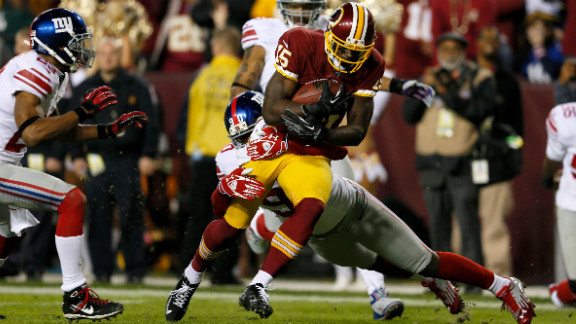 """Josh Morgan of the Washington Redskins runs the ball as he is hit by Jason Pierre-Paul of the New York Giants before scoring a touchdown after recovering a fumble on Monday, December 3, at FedExField in Landover, Maryland. Check out the action from Week 13 of the NFL, and <a href=""""http://www.cnn.com/2012/11/22/football/gallery/nfl-week-12/index.html"""">look back at the best photos from Week 12</a>."""