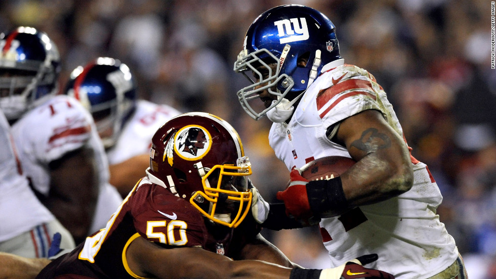 Ahmad Bradshaw of the New York Giants runs the ball Monday as he is hit by Rob Jackson of the Washington Redskins.