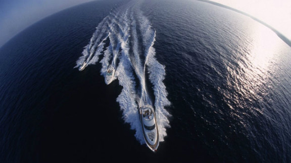 When not clambering up masts, the award-winning photographer can also be found hanging from a helicopter in a harness traveling 160 kilometres per-hour in hot pursuit of powerboats.