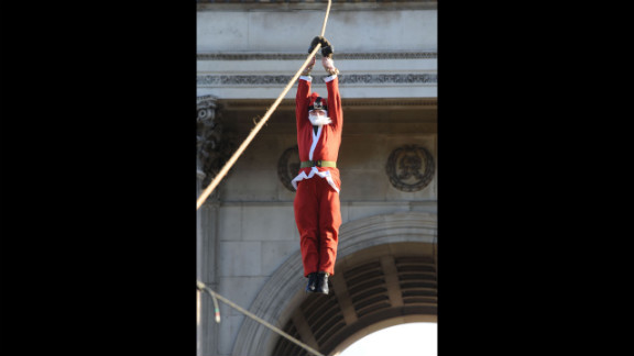 Santa descends on a rope during Christmas Box Launch at Wellington Arch in London