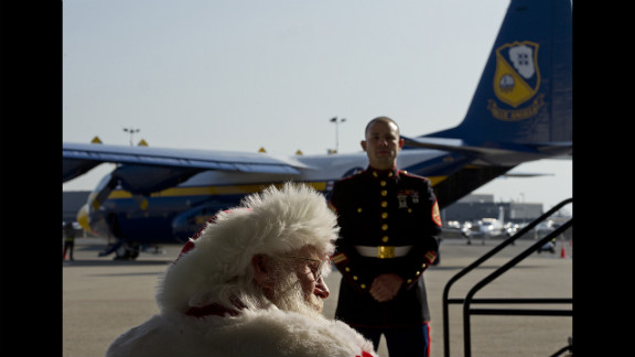 Santa Claus, aka Tim Connaghan, sits in the audience while a Marine stands guard during a presentation at Ronald Reagan National Airport on Monday, December 3, as part of the Marines