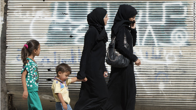 Syrian women walk past a closed shop in  Azaz. Violence against women is a big part of the war in Syria.