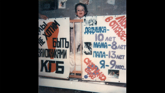 """The night before the Furmans took a final stand, their 9-month-old daughter Aliyah posed with posters, made by family friends. The one on the left reads in Russian, """"We don't want to be hostages of KGB!"""""""
