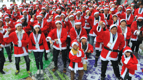 People in Santa Claus outfits imitate South Korean rapper Psy