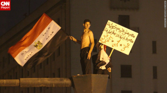"""At earlier protests, those gathered were """"hopeful and very determined,"""" said iReporter Sherine Mishriki, who sent in this image of youths <a href=""""http://ireport.cnn.com/docs/DOC-887373"""">waving flags and placards</a> in Cairo's iconic Tahrir Square on November 27."""