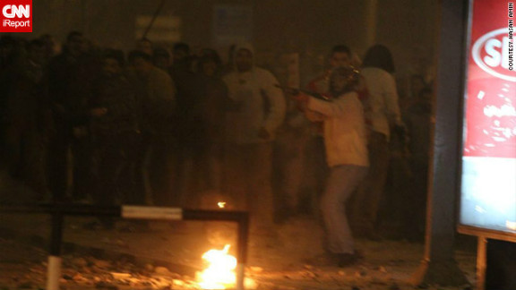 """On December 5, pro- and anti-Morsy protesters fought bloody battles on the streets outside the palace. Several deaths have been reported and hundreds of people have been injured, authorities say.  iReporter Hasan Amin said <a href=""""http://ireport.cnn.com/docs/DOC-891413"""">in this image</a>, a pro-Morsy supporter pointed what appears to be a rifle at protesters on the opposing side. The military rolled tanks into protest flashpoint areas, but many fear more violence ahead of a planned constitutional referendum on December 15."""