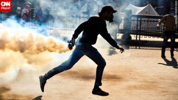 In this image by iReporter Hasan Amin, taken on November 27, a protester is captured preparing to throw back a tear gas canister fired by police.