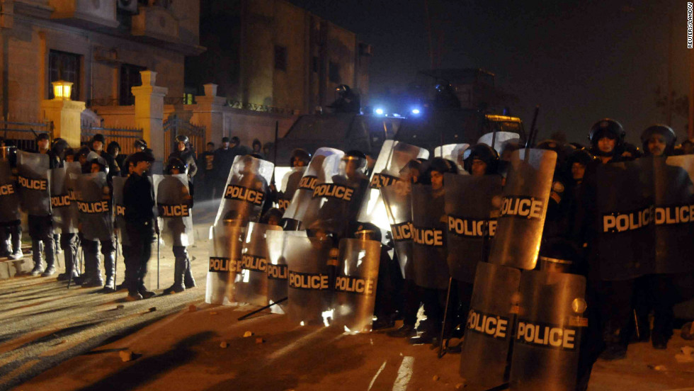 Riot police form a line as anti-Morsy protesters surge around the Muslim Brotherhood's headquarters in Cairo on December 6.