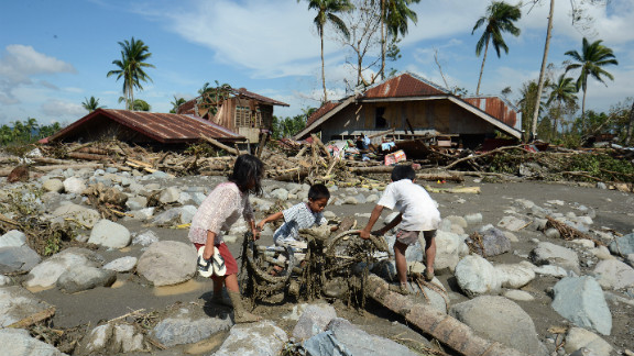 Children retrieve a bicycle among boulders near destroyed houses in New Bataan on December 6.