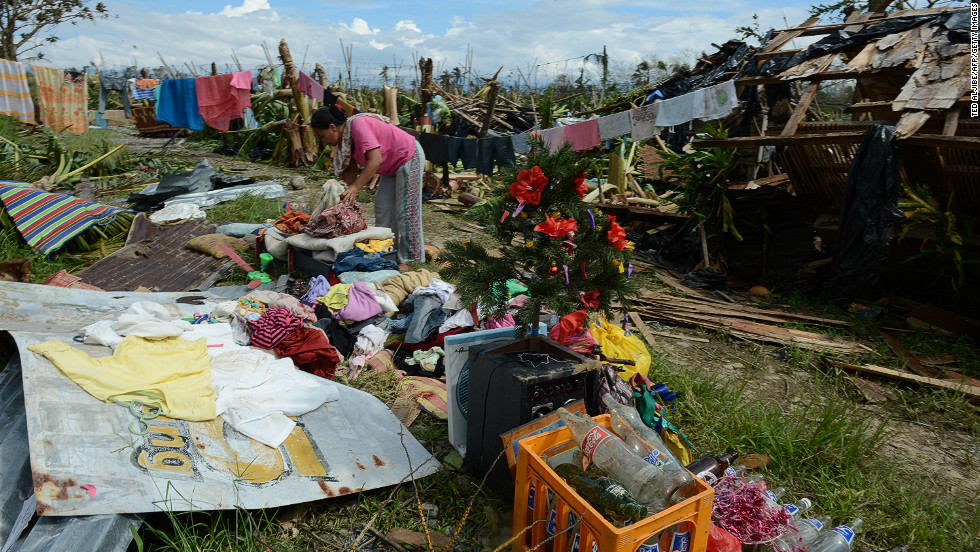 A woman sorts out clothes and belongings in front of her damaged house in Montevista on December 5.