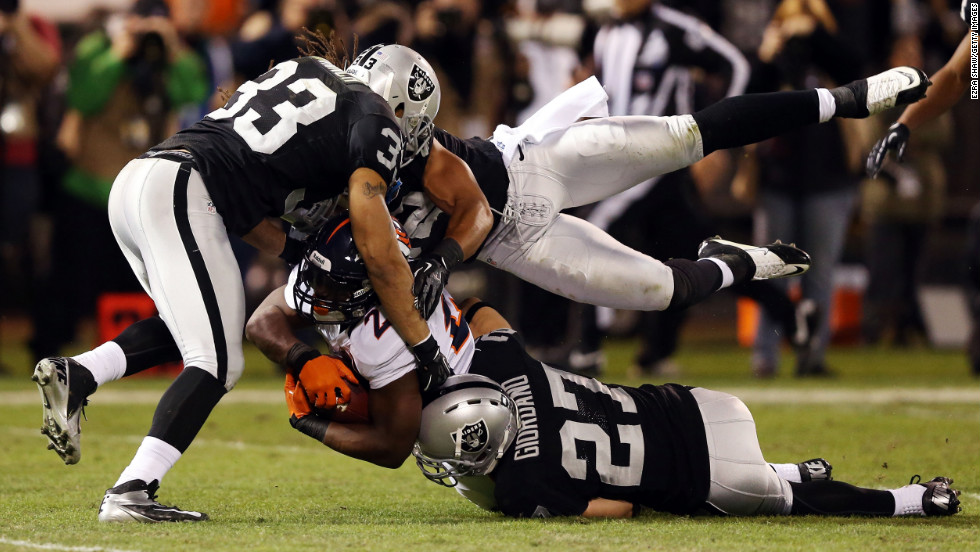 Knowshon Moreno of the Denver Broncos gets tackled by three Oakland Raiders players during second quarter on Thursday.