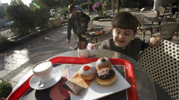 "A young Israeli boy looks at a serving of fresh oil-fried and jam-filled doughnuts, known in Hebrew as ""sufganiyot"", served at one of the local bakeries in Kadima, central Israel, during Hanukkah."