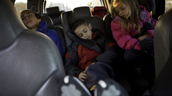 Tim, 15, Christian and Carly rest on their way to a bus that will take them to school. Their family has temporarily relocated from Broad Channel section of Queens to an apartment in Brooklyn.