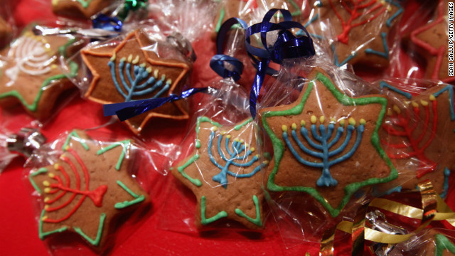 Gingerbread cookies in the shape of Stars of David and decorated with a Hanukkiah candelabrum.