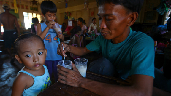 A man feeds his children at an evacuation center for victims of Typhoon Bopha in the town of Maparat in Compostela Valley province on December 8.