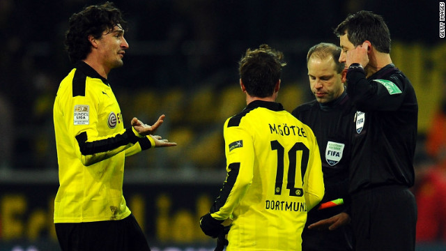 Borussia Dortmund's Mats Hummels, left, and Mario Gotze confront referee Wolfgang Stark after Saturday's defeat.