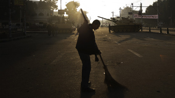 An Egyptian protester sweeps the street near army tanks deployed outside the presidential palace in Cairo on December 8, after continued protests overnight.