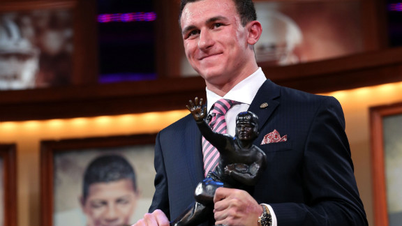 Quarterback Johnny Manziel of the Texas A&M University Aggies poses with the Heisman Memorial Trophy after being named the 78th Heisman Memorial Trophy Award winner at the Best Buy Theater on December 8 in New York City.