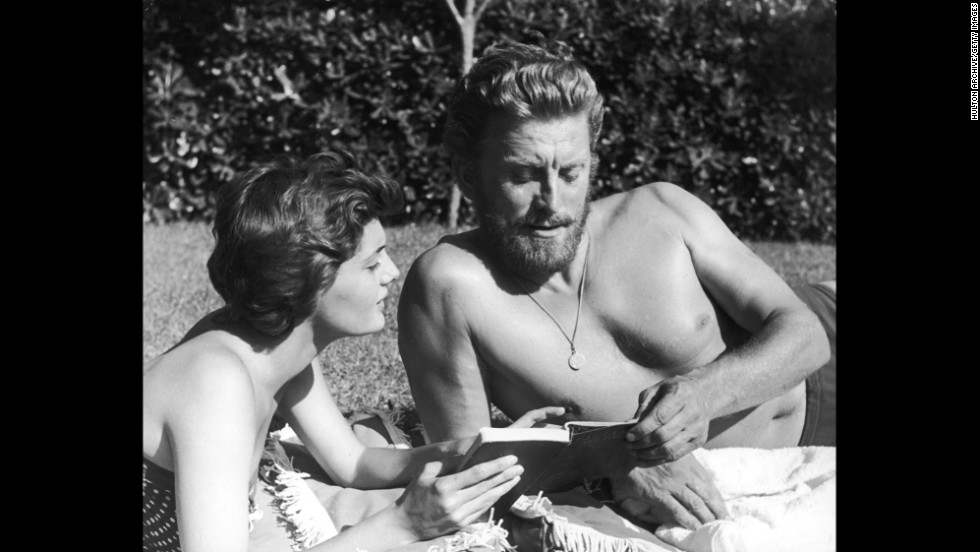 Kirk Douglas enjoys a book with his second wife, Anne Buydens, circa 1956. The two have been married since 1954.