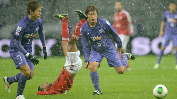 Al-Ahly midfielder Hossam Ashour takes a tumble as he fights for the ball with Sanfrecce Hiroshima