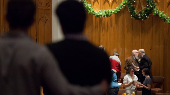 Larry Duncan and Randy Shepherd kiss at the end of a mass wedding for 25 couples in Seattle on December 9 in Seattle.