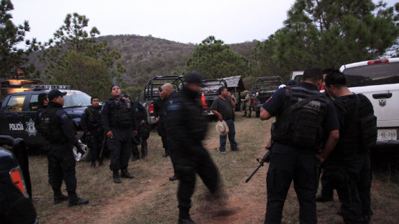 "Federal police work near the site of the plane crash in Iturbide, Mexico. ""The aircraft was destroyed, totally fragmented,"" an aviation official told CNN affiliate Televisa. Six others were killed, including the singer"