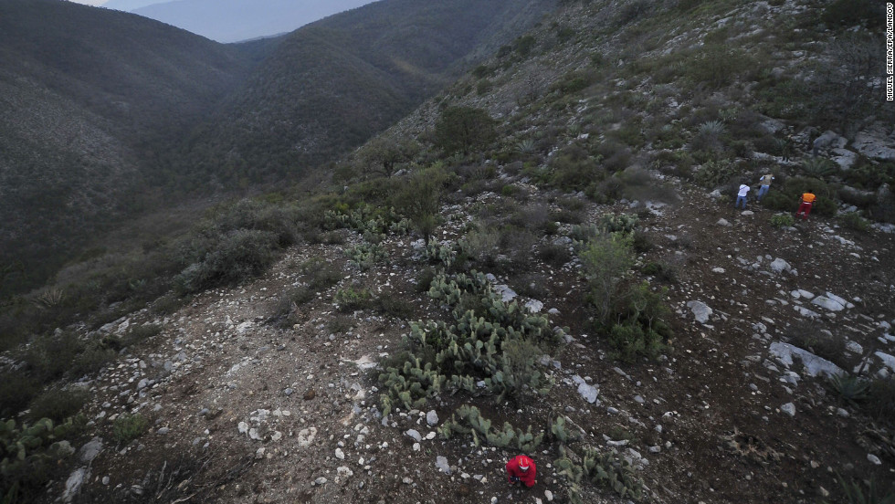 Workers search around the accident scene in Mexico's Sierra Madre Oriental mountain range.