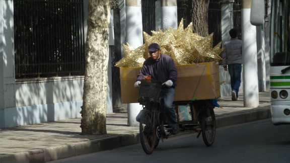 """Dutch iReporter <a href=""""http://ireport.cnn.com/people/Irenere"""">Irene Reijs</a>, captured this image of a man delivering Christmas decorations by bike in her adopted home of Shanghai, China. """"Christmas is not a Chinese tradition, but much of our decorations are made in China,"""" she said."""