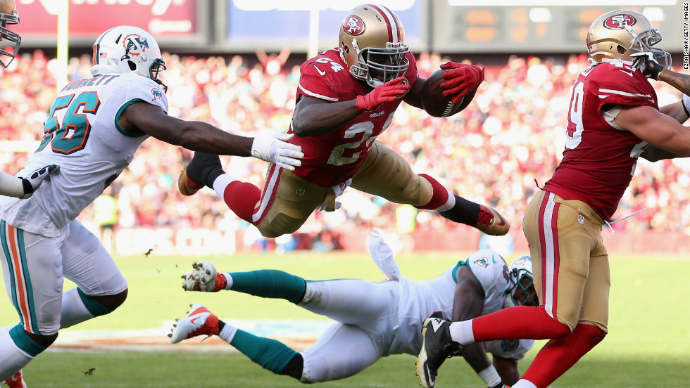 San Francisco 49ers running back Anthony Dixon leaps over safety Chris Clemons of the Miami Dolphins at Candlestick Park on Sunday in San Francisco, California.