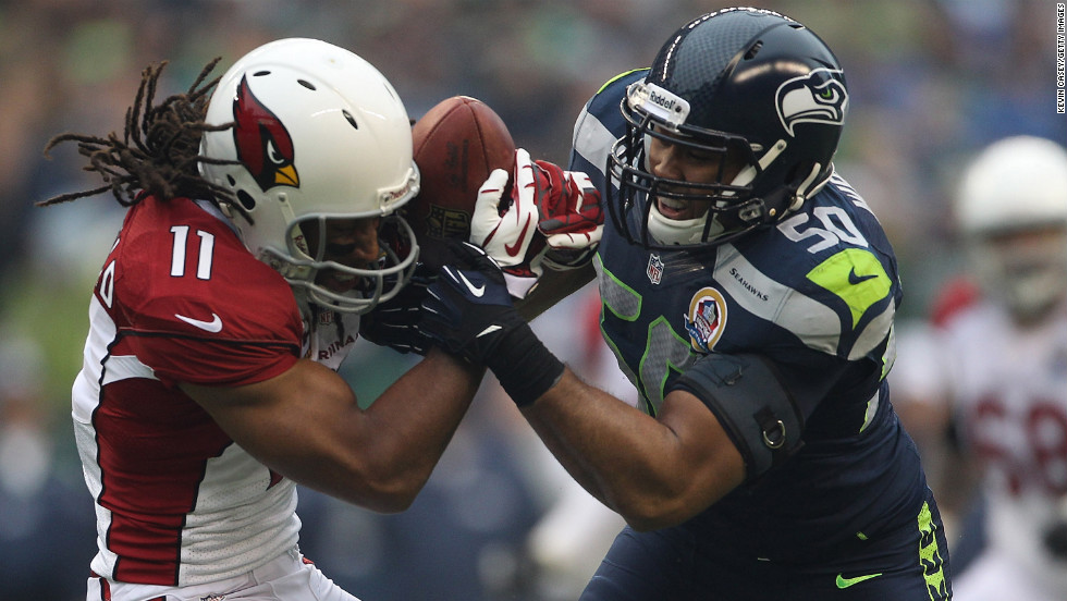 Seattle Seahawks linebacker K.J. Wright  tries to wrestle the ball away from Arizona Cardinals wide receiver Larry Fitzgerald during the first quarter on Sunday.
