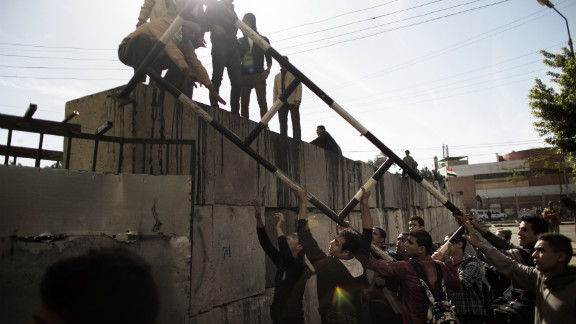 Protesters remove part of a metal barrier protecting the presidential palace on December 11.