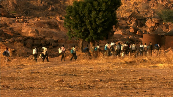 """In the film """"Erasing the Nuba"""" Rwandan-born journalist Yoletta Nyange documented the plight of the Nuba people. In this scene from the film, a column of refugees flees to the Yida refugee camp in South Sudan."""