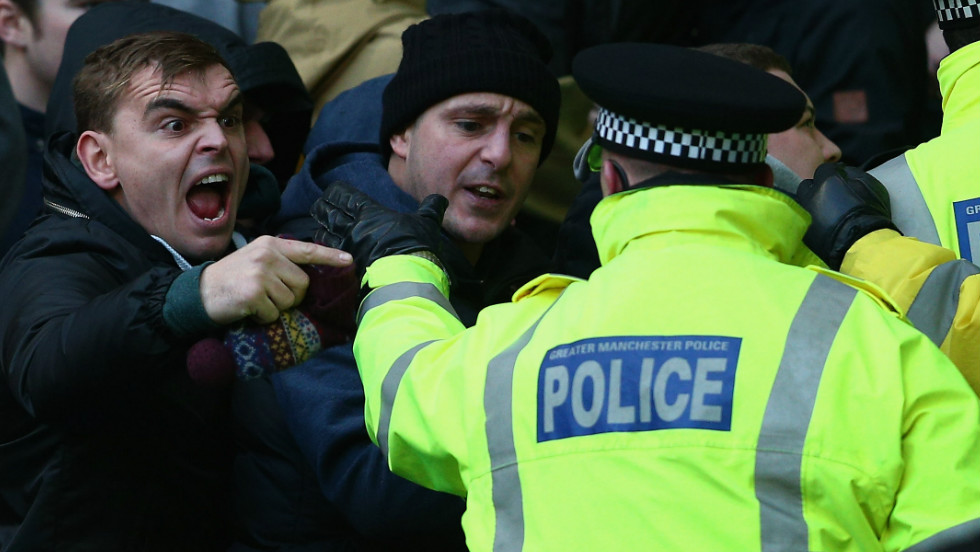 A total of 13 fans were arrested and nine charged -- one with making alleged racist chants. Here a City supporter shouts across the police security cordon.