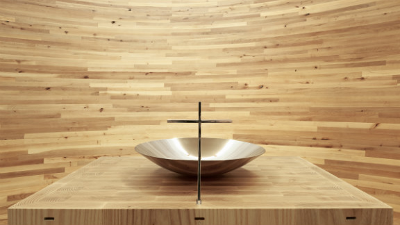 Inside the Kamppi Chapel, the curving inner wall is made out of alder planks into a closed space with light falling from above.