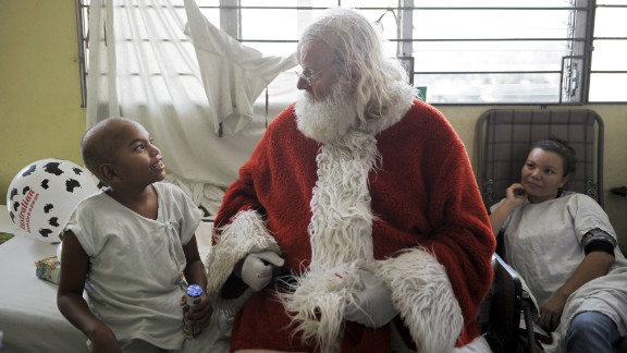Icelandic philantropist Einar Sveinsson, dressed as Santa Claus, speaks with a patient in the oncology ward during a visit to the Benjamin Bloom National Children
