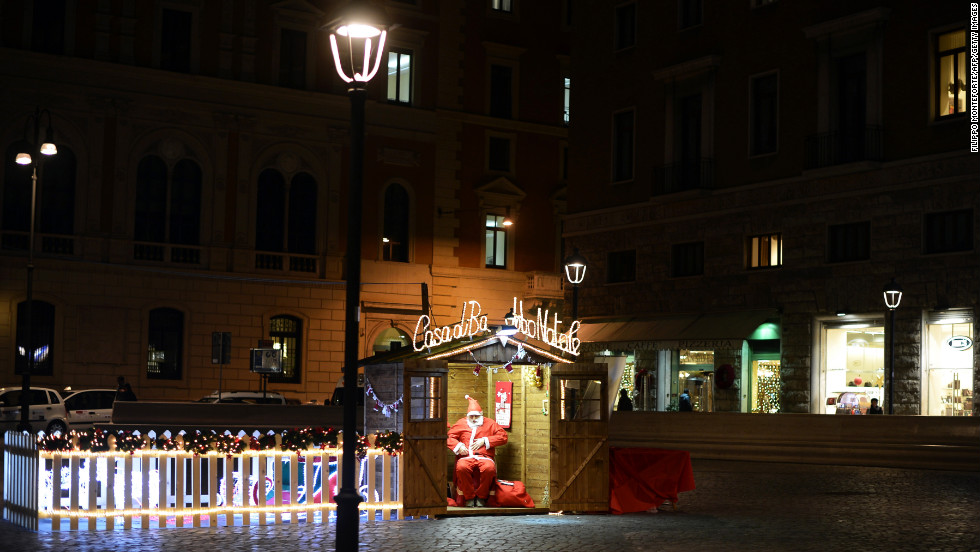 A man dressed as Santa waits for customers in a wooden house in Rome on December 11.