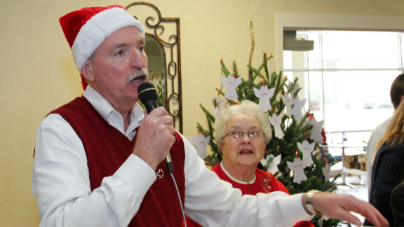 Mark Kelly reaches for a door prize to give away at the third annual Bob Buechner Holy Cross Blood Drive.