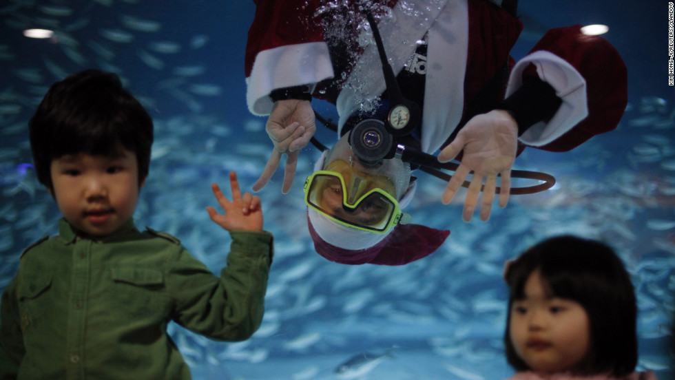 "A diver dressed as Santa Claus poses for a photograph with children during a promotional event for the ""Sardines Feeding Show with Santa Claus"" at the Coex Aquarium in Seoul, South Korea, on December 11."