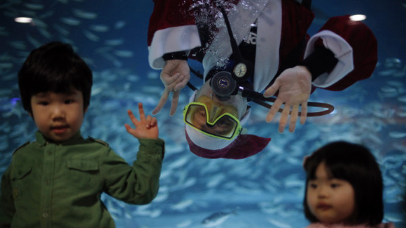 """A diver dressed as Santa Claus poses for a photograph with children during a promotional event for the """"Sardines Feeding Show with Santa Claus"""" at the Coex Aquarium in Seoul, South Korea, on December 11."""