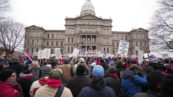 Thousands of people, many of them union workers, gathered outside the statehouse, chanting and holding signs as snow fell.
