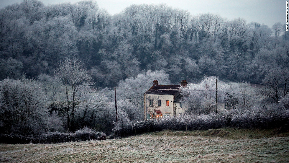 Frost lingers on trees surrounding a house near Wells on December 12 in Somerset, England.