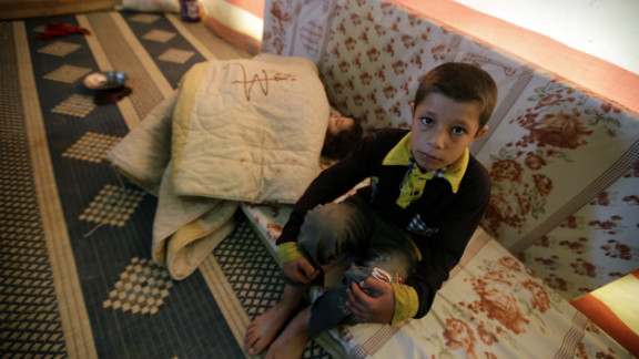 A Syrian refugee child sits near his sleeping sister at his family