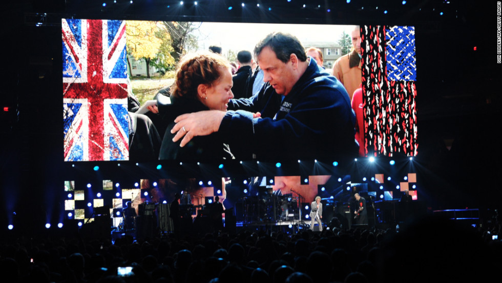 "A video shows New Jersey Gov. Chris Christie speaking to a victim of Hurricane Sandy as The Who perform on stage during ""12-12-12: The Concert For Sandy Relief."" The 2012 concert at New York's Madison Square Garden was held to benefit The Robin Hood Relief Fund to aid the victims of Superstorm Sandy."